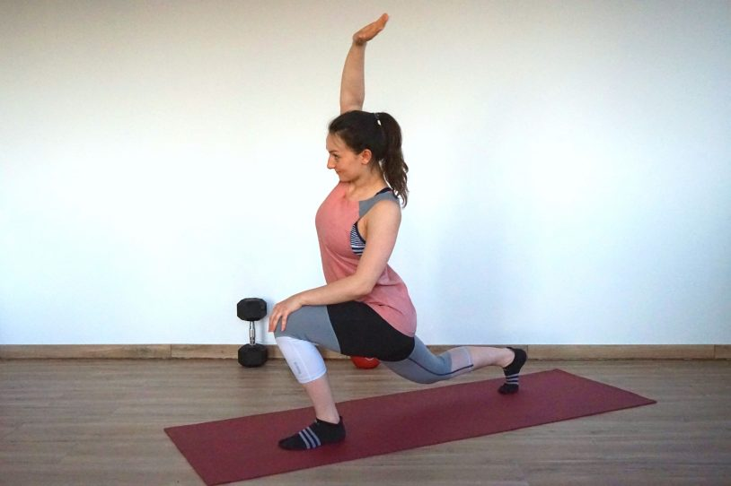 Young woman in sports outfit performing forward lunge with psoas reach on a yoga mat.
