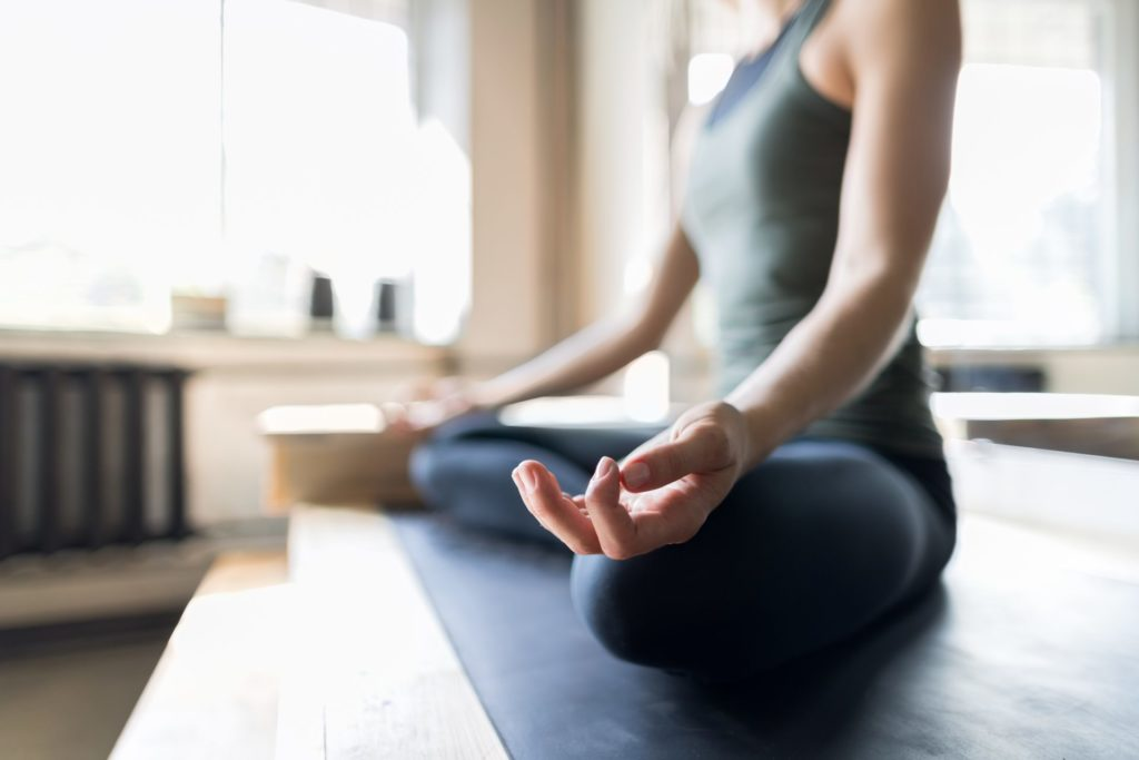 """A meditating woman trying to reduce stress and heal her autoimmune disease from the article """"take control over autoimmune disease naturally"""""""