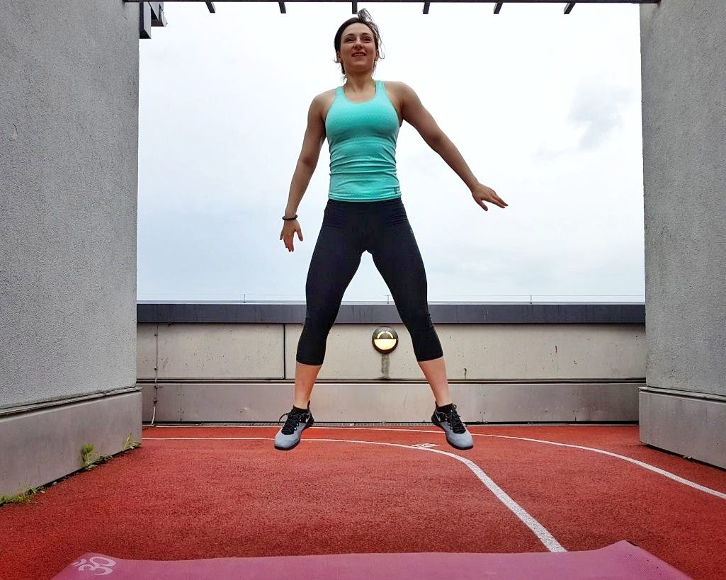 girl in sports clothes doing a bodyweight crossfit workout jumping squat