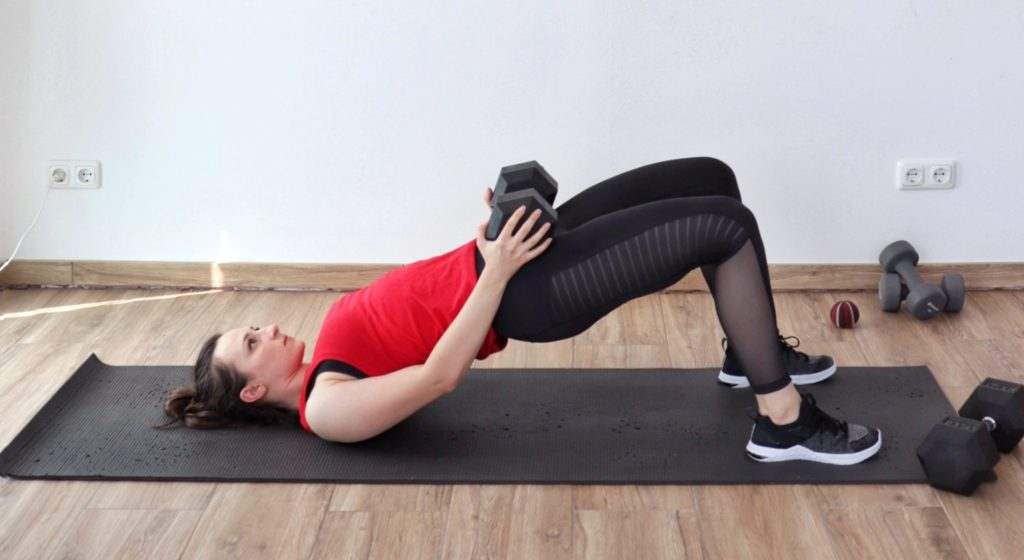 Young woman demonstrating the weighted glute bridge