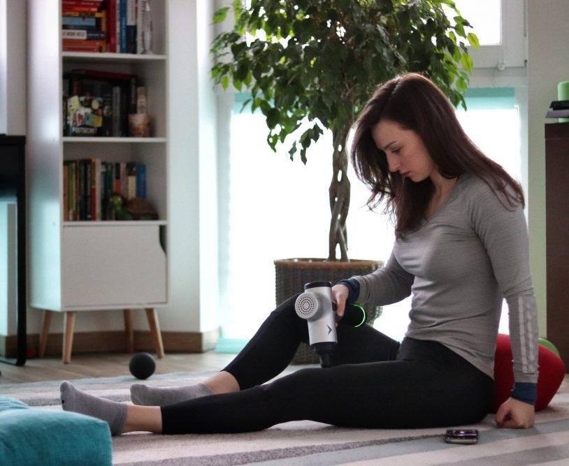 Girl using the Hyperice Hypervolt massage gun device.