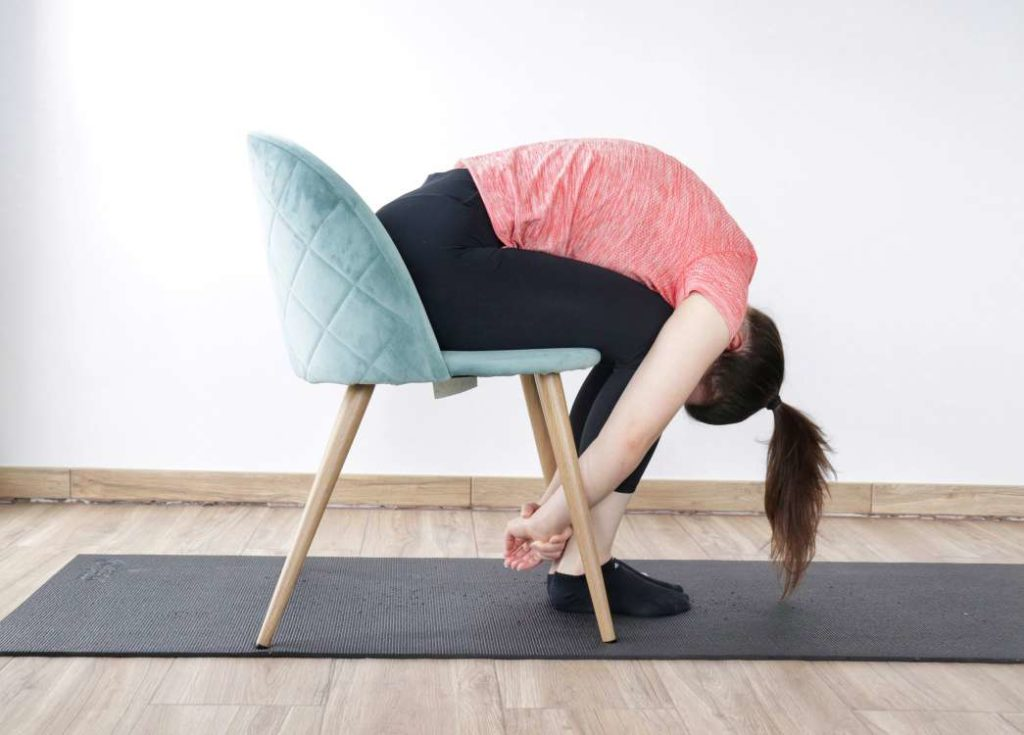 Seated forward  fold on a chair stretching exercise demonstation for correcting anterior pelvic tilt.
