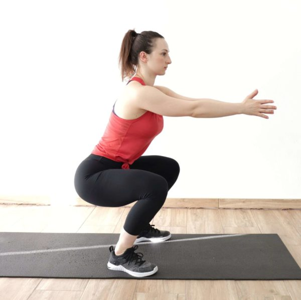"""image of a young woman demonstrating the squat from the article """"Top 8 Glute Exercises to Build and Shape your a strong Ass"""""""