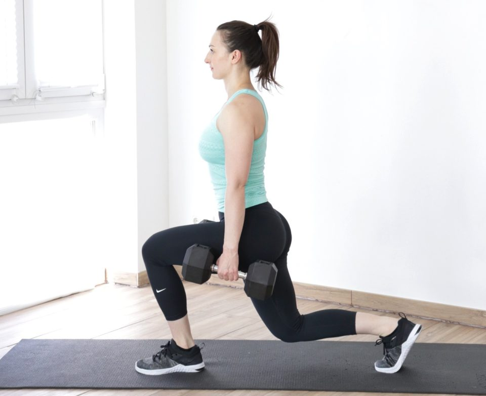 A young fit woman performing a beginner dumbbell execise - walking lunges.